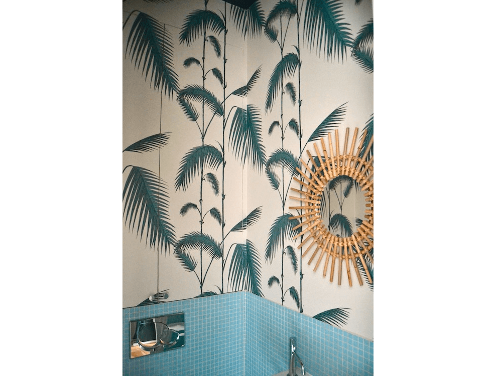 Les toilettes d'un appartement parisien décorées avec le papier peint Palm Leaves de Cole and Son. Projet de Caroline Andréoni. Crédit photo : Au fil des Couleurs